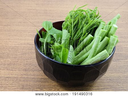Vegetable A Bowl of Fresh Green Cowpeas Leucaena Leucocephala and Gotu Kola Leaves on Wooden Table with Copy Space for Text Decorated.