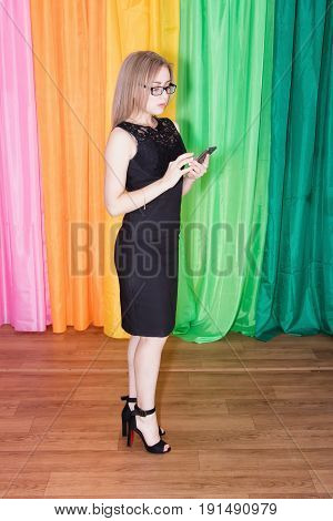 Young Seductive Girl In A Black Dress And Sunglasses Holding A Smartphone