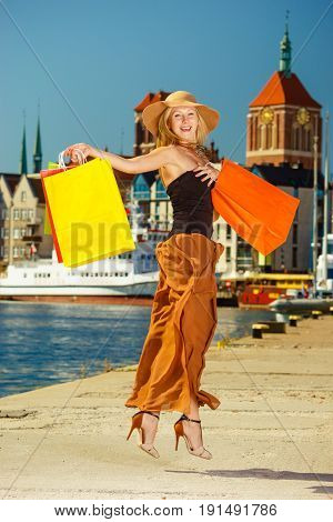 Spending money on sales buying things concept. Fashionable woman happy jumping with shopping bags wearing glamorous outfit and big sun hat