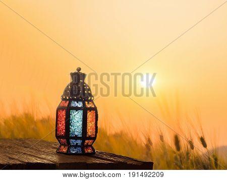 Candle light lids on muslim style's lantern shining on floor with colorful vintage pattern on surface use as greeting on ramadan kareem mubarak