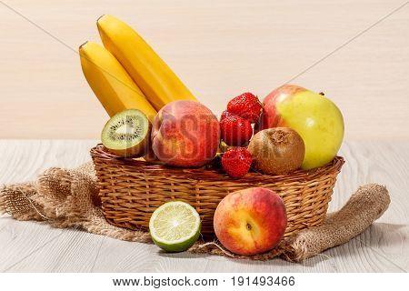 Fresh Strawberries, Nectarine, Lime, Kiwi, Banana, Apple In A Wicker Basket On The Table