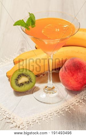 Orange Jelly In The Glass Topped Mint Leaves And Fruits On The White Napkin