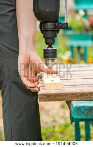 Photo of man with drill screwing board to bench in park