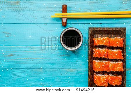 Photo rolls on board, with yellow sticks, soy sauce on blue table