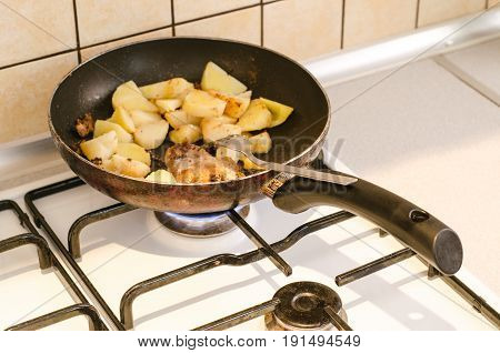 a potatoes and meat on a stove