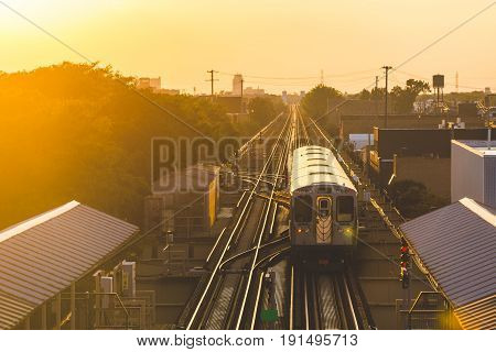 Subway train at sunset in Chicago. Panoramic view of elevated tracks and station at sunset with train leaving. Travel and transportation concepts.