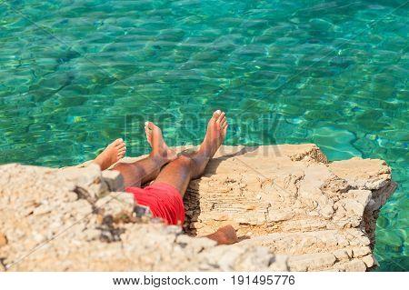 Young tourists sunbathe on mediterranean rocky beach