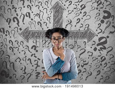Thoughtful businesswoman in front of wall with arrow symbol and question marks