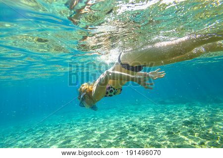 Female apnea bikini swims in crystal sea. Underwater background of a woman snorkeling and doing skin diving. Watersport activity in summer vacations. Tropical destination holidays concept.