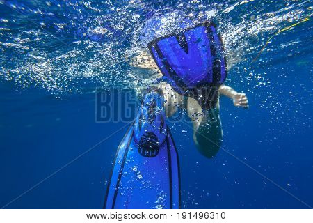 Closeup of blue fins of underwater female apnea while swimming. Bubbles of water. View from behind snorkeler woman in underwater activity. Watersport and leisure concept. Fins slamming into sea.