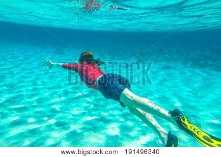 Man with mask snorkeling in clear water. Underwater background of a man snorkeling and doing free diving. Watersport activity in summer vacations. Tropical destination holidays concept.