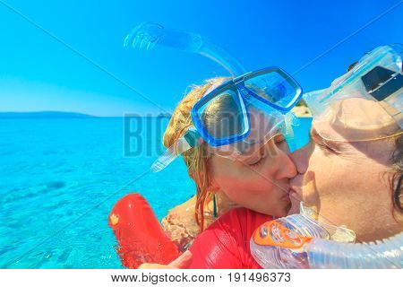Couple with snorkeling equipment kissing in tropical sea.Snorkel couple enjoying in romatic vacations. Summer holidays watersport concept. Leisure and sport in crystal waters.Young couple on honeymoon