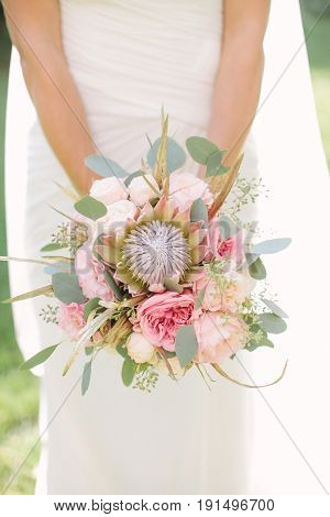 elegant bride in a white dress and veil holding in hand a wedding bouquet from gently pink roses, peonies and eucalyptus , outdoor. Tenderness, love, wedding, summer mood - concept.
