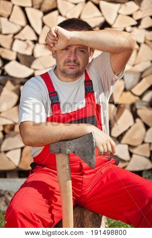 Tired worker done chopping and stacking the firewood - wiping forehead with one arm and resting the other on axe