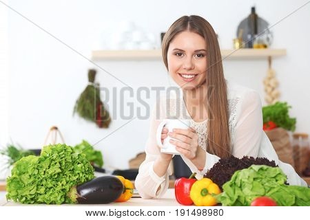 Young happy woman is holding white cup and looking at the camera while sitting at wooden table in the kitchen among green vegetables. Housewife is looking for a new recipe for  cooking or having morning coffee