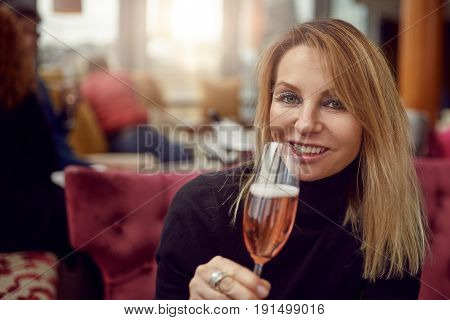 Attractive woman drinking a glass of champagne as she celebrates a special event in a restaurant looking at the camera with a warm smile