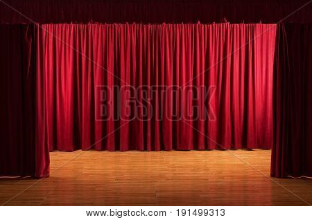 Old stage with worn floor - theatrical scene with open red curtains