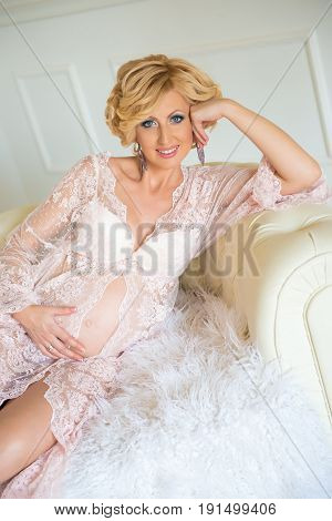 Young happy pregnant woman sitting on sofa in white lace dressing gown
