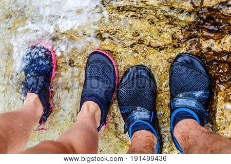Young couple in water shoe standing on rocky beach