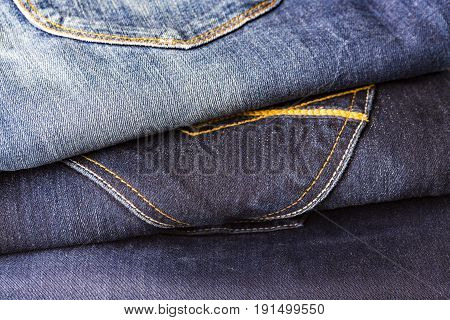 Pile of different blue jeans on white table