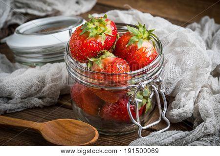 Strawberry In Jar On Wooden Background.