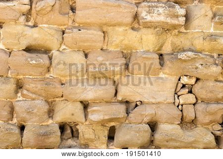 Antique eroded uneven stone wall texture. Horizontal background