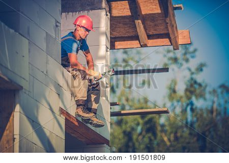 House Building. Contractor Taking Break While Resting Within Future Window Area. Construction Worker with Leveling Tool.