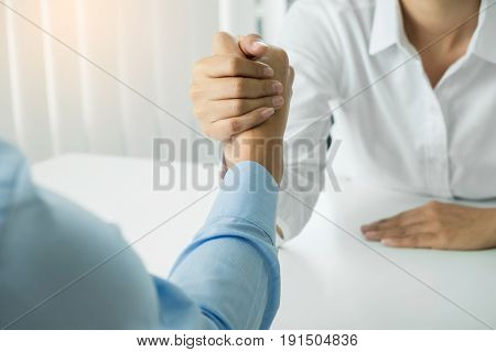 two clasped hands of businessmen in office.