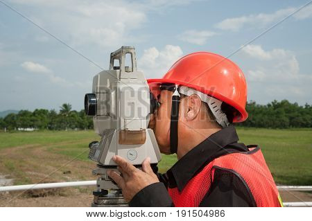 Surveyor or Engineer making measure by Theodolite on the field.