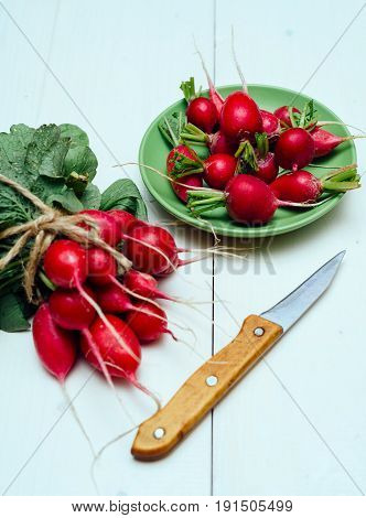Bunch of fresh organic red radishe with tops and green leaves near plate with radish and knife on white wooden background. Vegetable background