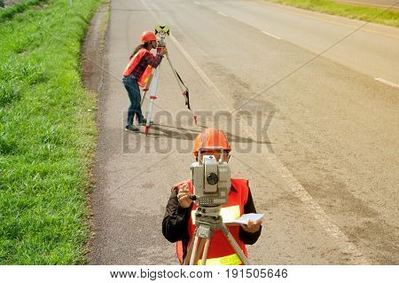 Surveyor or Engineer making measure with partner by Theodolite and prism reflector on the highway.