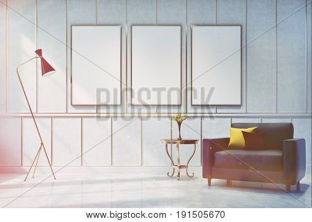 White living room interior with a poster gallery on the wall. There is a gray armchair with cushions in the corner and a coffee table with a flower vase. 3d rendering mock up toned image