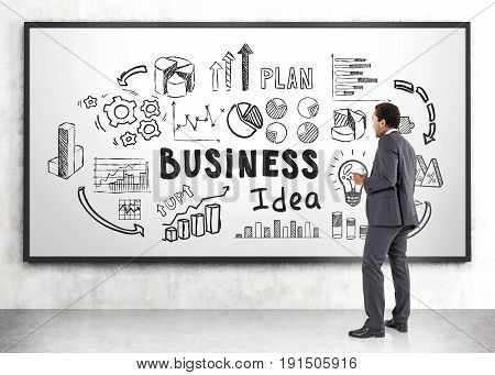 Side view of an African American businessman in a dark gray suit standing and holding a coffee to go near a whiteboard with a business idea sketch.