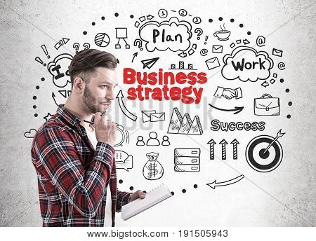 Side view of a bearded young man in a checkered shirt and a white T shirt holding a notebook and a pen and thinking. Concrete wall with a business strategy sketch on it.