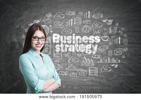 Young businesswoman wearing glasses and a blueish shirt standing with crossed arms and smiling. Blackboard with a business strategy sketch