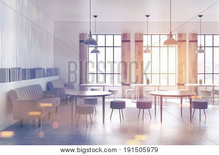 Side view of a modern cafe interior with concrete walls and floor round tables and chairs and beige sofas near tall windows and bookshelves. 3d rendering mock up toned image