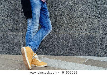 Man's feet in jeans and trendy shoes free space. Man with orange shoes standing on textured concrete city street.Close-up view of man's leather shoes