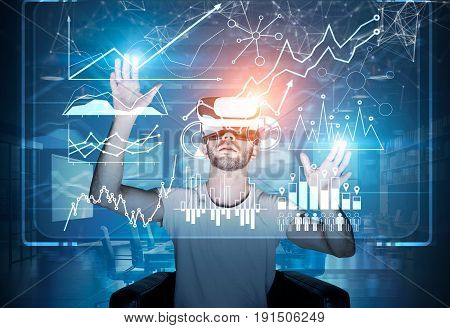 Front view of a bearded man wearing a T shirt and VR glasses and sitting in an armchair interacting with graphs and holograms in the air. Toned image double exposure