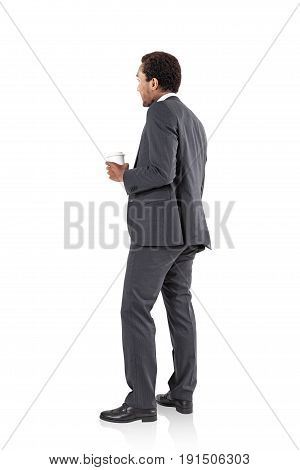 Side view of an African American businessman in a dark gray suit standing and holding a coffee to go. Isolated portrait.
