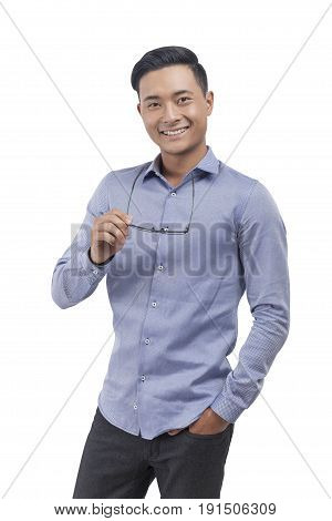 Isolated portrait of a smiling Asian businessman wearing a blue shirt and dark trousers and holding glasses. Concept of success and happiness