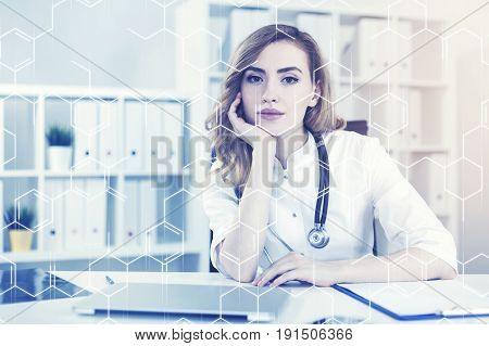 Portrait of a woman doctor with red hair sitting at her workplace in a white office with a laptop on the desk. Toned image film effect