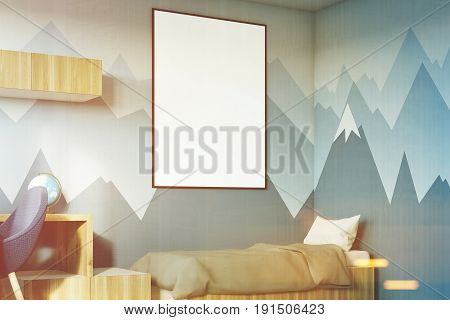 Side view of a kids room interior with a poster hanging above a bed bookshelves and a blue chair.  3d rendering mock up toned image
