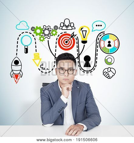 Portrait of a young Asian businessman wearing glasses and a blue suit and sitting at a table. Concept of decision making. Concrete wall colorful start up sketch