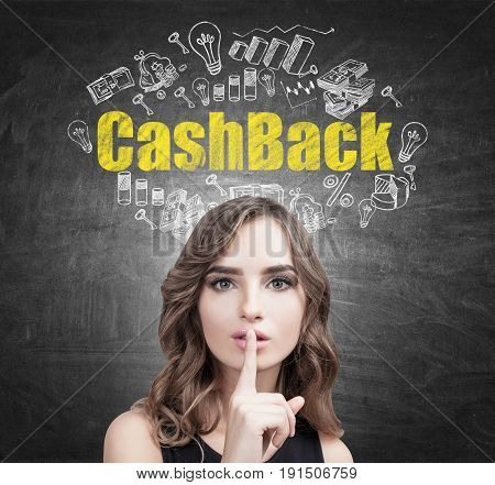 Close up of a young European woman with wavy hair making a hush sign. Blackboard background with a cashback sketch on it.