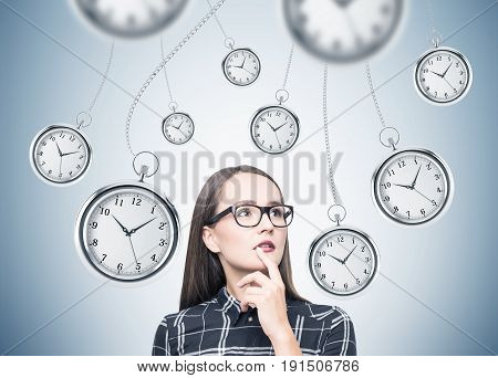 Portrait of a nerdy girl in glasses standing near a gray wall with many stopwatches hanging on chains. Concept of a deadline