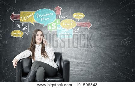 Young businesswoman with fair hair smiling and sitting in a leather armchair and talking on her smartphone. Blackboard with a business scheme