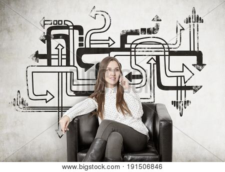 Young businesswoman with fair hair smiling and sitting in a leather armchair and talking on her smartphone. Concept of business communication. Concrete wall background with arrow labyrinth