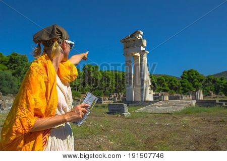 Tourist woman in Greek dress indicates the ruins of Temple of Asklepieion, Epidaurus, Peloponnese, Greece. The Sanctuary of Asclepius is a famous heritage site.Mediterranean travel and tourism concept