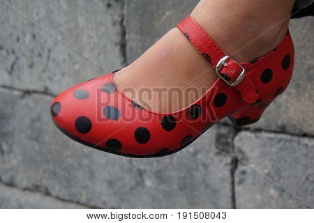 Red dotted Spanish flamenco dancing shoe against a bricked background