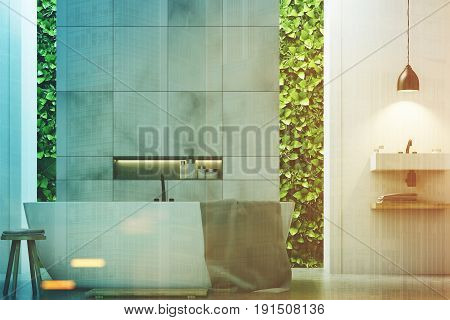 Eco bathroom interior with two narrow windows green shrubbery is seen through. There are two sinks by the sides of a white tub standing near a marble wall. Close up. 3d rendering mock up toned image